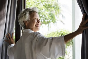 Senior woman opening the curtains