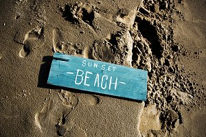 Wooden sign on the sand (PSD)
