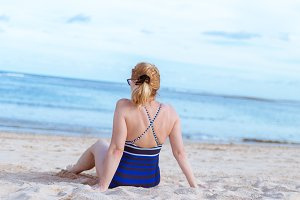 Senior woman on the beach. Travel vacation to Bali island.