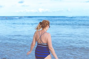 Senior woman on the beach. Travel vacation to Bali island.