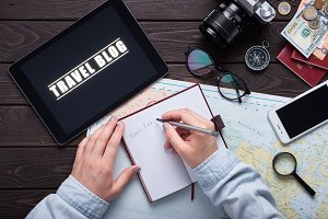 Woman watching online video and writing plan trip. Planning travel. Camera, maps, phone, notepad with money. Thirst travel.
