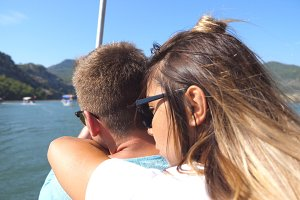 Rear back view of young couple spending time together on deck of sailboat at sunny day. Beautiful girl hugging her boyfriend from behind on boat during trip. Vacation or holiday concept. Close up