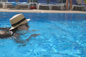 Young beautiful girl in sunglasses and hat swimming in pool. Woman relaxing in clear warm water on sunny day. Summer vacation or holiday concept. Close up Slow motion