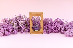Sand running through the bulbs of an hourglass measuring the passing time in a countdown to a deadline, on a flower lilac spring background with copy space.