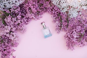 Glass jar and lilac flowers on the background for spa and aromatherapy, copy space for text.