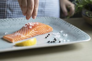 Person seasoning a fillet of salmon