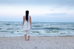 Back view of beautiful woman in white dress with dreadlock on the head enjoying the idyllic scene on the beach.