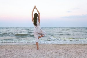 Yoga meditation woman meditating at beach sunset relaxing in yoga posture, tree pose, vrksasana. Relaxed serene woman enjoying evening sun light and sunshine