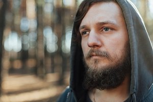 close up portrait of a bearded hipster tourist in gray hood man in the sunlight woods forest