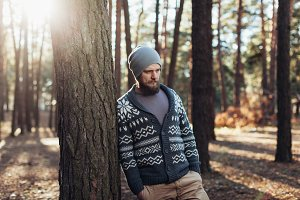 a young man with a beard walks in a pine forest. Portrait of a brutal bearded man Autumn forest