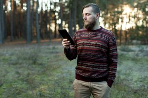 Portrait of adult man walking in the pine forest with digital tablet.
