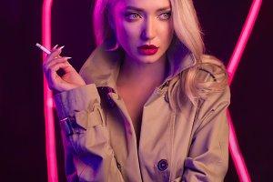 Fashion art photo of elegant model in seductive wear with light neon colored club spotlights