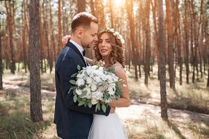 Sunshine portrait of happy bride and groom outdoor in nature location at sunset. Warm summertime
