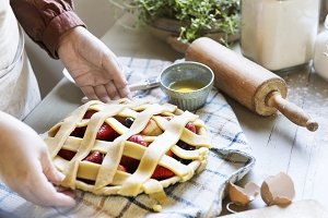 A person baking fruit pie