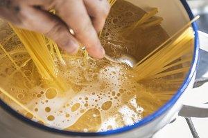 A chef boiling capellini pasta