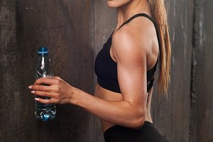 Young athletic woman in sportswear drinking water in studio against black background. Ideal female sports figure. Fitness girl with perfect sculpted muscular and tight body.