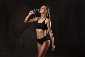 Image of muscular young female athlete wearing black sport wear standingon dark background. Woman bodybuilder resting after workout. Drink water