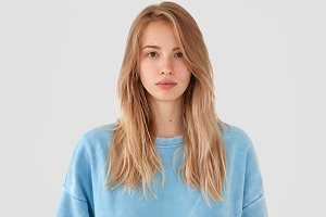 Portrait of confident pretty young woman with fair hair, dressed in casual blue oversized sweater, has healthy skin, looks directly into camera, isolated on white background. People, facial expression