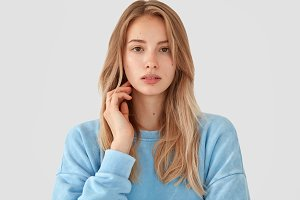 Portrait of beautiful European femae with tender look, has pleasant appearance and healthy skin, poses indoor against white background, wears casual long sleeved light blue sweater. People, lifestyle