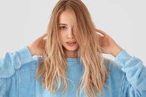 Close up portrait of mysterious female has luxurious hair, wears casual blue sweater, looks confidently at camera, poses against white background. People and youth concept. Tender woman poses indoor