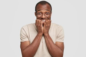 Excited young African American guy clenches teeth and grins at camera, doesn`t expect to recieve present, wears spectacles, looks at camera with nervous expression, isolated on white background