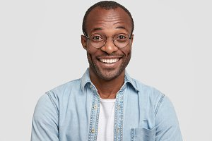 Portrait of happy cheerful dark skinned male laughs joyfully, works in restaurant, greets new visitors, wears spectacles and denim shirt, isolated over white background. Positive human emotions