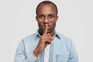Keep this in secret! Serious dark skinned man keeps voice down, shows silence sign with index finger over mouth, asks to be quiet, wears round spectacles, isolated on white concrete background