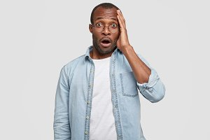 Confused and shocked dark skinned male being surprised with what happening, looks with terrified expression at camera, isolated on white background. African American guy hear shocking rumor.
