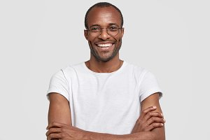 Portrait of unshaven pleased dark skinned male has warm broad smile, keeps hands crossed, rejoices hearing positive news, wears casual white t shirt and glasses. People and positive emotions