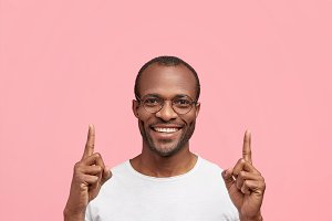 Positive African American male in casual outfit, smiles broadly from satisfaction, points with fore fingers upwards, cannot stand calm, isolated over pink background. People and advertisement concept