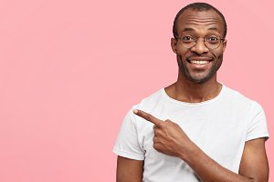 Glad unshaven dark skinned male with positive expression, wears casual white t shirt and spectacles, indicates at blank copy space with fore finger, happy to advertise something. Horizontal shot