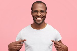 Look there, perfect copy space. Happy attractive African American guy with cheerful expression indicates at white t shirt, shows place for your advertisement or logo, isolated on pink background.
