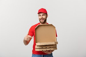 Pizza delivery concept. Young boy is delivering and showing pizza boxs in boxes. Isolated on white background