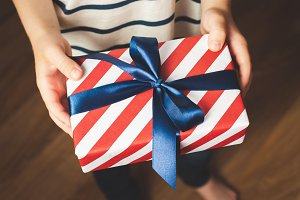Kid's hands holding gift box.