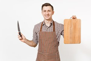 Young smiling man chef or waiter in striped brown apron, shirt holding wooden cutting board, knife isolated on white background. Male housekeeper or houseworker. Domestic worker for advertisement.