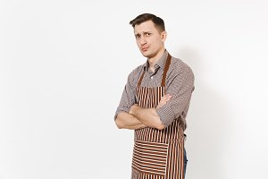 Young skeptic upset man chef or waiter in striped brown apron, shirt holding hands folded isolated on white background. Male housekeeper, houseworker looking camera. Domestic worker for advertisement.