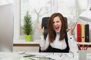 Pretty angry business woman in suit sitting at the desk with tablet, working at computer with modern monitor with documents in light office, swearing and screaming, resolving issues, emotion concept
