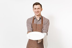 Young man chef or waiter in striped brown apron, shirt holding white round empty clear plate, towel napkin isolated on white background. Male housekeeper or houseworker. Domestic worker, copy space.