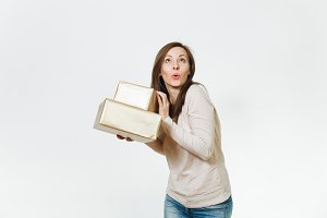 Pretty caucasian fun young happy woman in light clothes with shy charming smile, brown hair and two golden gift boxes with present, celebrating holiday on white background isolated for advertisement.