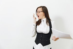 Tired sleepy caucasian young brown-hair business woman in black suit, white shirt and glasses with work documents yawning isolated on white background. Manager or worker. Copy space for advertisement.