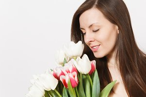 Close up portrait of beautiful young brunette girl is holding bright bouquet of white and pink tulips in hands, smiling with closed eyes in studio on white background. Celebration, good mood concept.