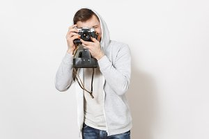 Young handsome smiling man student in t-shirt and light sweatshirt with hood with headphones takes pictures on retro camera with cover isolated on white background. Concept of photography, hobby