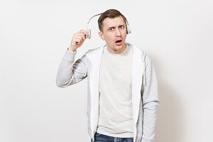 Young handsome man student in t-shirt and light sweatshirt listening to music with white wireless headphones and in perplexity removes them in studio on white background. Concept of emotions