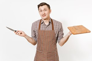 Young bewildered man chef or waiter in striped brown apron, shirt holding wooden cutting board, knife isolated on white background. Male housekeeper or houseworker. Domestic worker for advertisement.