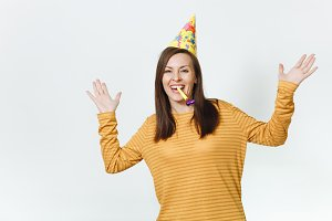 Pretty caucasian fun young happy woman in yellow clothes and birthday party hat with brown long hair, playing pipe, celebrating holiday, spreading hands on white background isolated for advertisement.