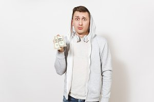 Young handsome man student in t-shirt, blue jeans and light sweatshirt with hood with headphones holds two one-dollar bills and perplexedly looks in studio on white background. Concept of emotions