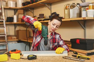 Beautiful caucasian young brown-hair woman in plaid shirt and gray T-shirt working in carpentry workshop at table place, drilling with drill holes in piece of iron and wood while making furniture.