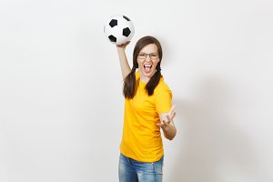Crazy fun European woman, two fun pony tails, football fan or player in glasses, yellow uniform hold classic soccer ball isolated on white background. Sport, play, football, healthy lifestyle concept.