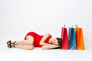Glamour caucasian fashionable young brown-hair woman in red dress lying down, sleeping at multi colored packets with purchases after shopping isolated on white background. Copy space for advertisement