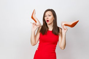 Attractive glamour caucasian fashionable young pensive perplexed brown-hair woman in red dress getting beige shoes with red sole of shopping isolated on white background. Copy space for advertisement.